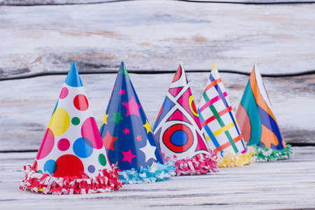 Holiday hats on wooden background. Set of Birthday caps on wooden planks.