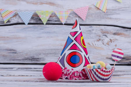 Background with kids Birthday party items. Party hat, sweets and clown sponge nose on wooden background. Childrens Birthday supplies.