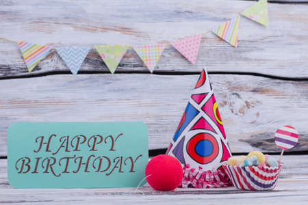 Happy Birthday background. Party hat, candies, clowns red nose and card with inscription Happy Birthday. Banco de Imagens