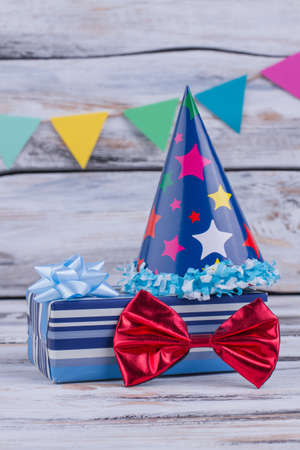 Festive stuff for Birthday party. Party hat, gift box and red bow on wooden background. Banco de Imagens