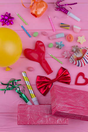 Blowers, balloons, candles and sweets. Birthday party items and accessories on pink wooden background.