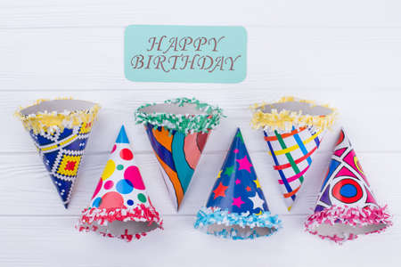 Happy Birthday composition with party hats. Flat lay composition with Birthday party caps and card with inscription Happy Birthday.