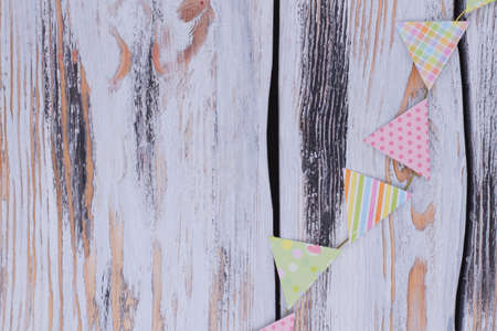 Birthday paper flags on rustic background. Decorative party flags on vintage wooden background with copy space.