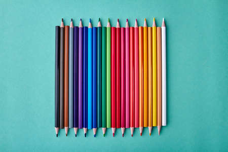 Row of multicolored pencils on color background. Set of colorful pencils on turquoise background. Concept of school supplies.