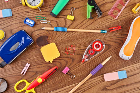 Sfondo della scuola con diversi rifornimenti. Vari accessori per studenti su fondo in legno. Concetto di educazione.