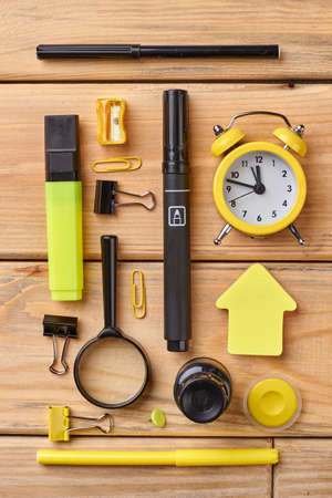 Set of school supplies, top view. Alarm clock, magnifying glass, markers, sticky note and other school accessories on wooden table.