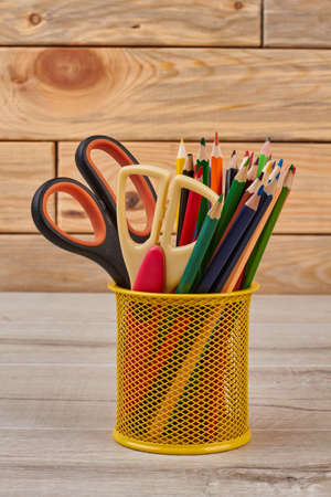 Colored pencils in basket. School or office supplies on wooden background. Stockfoto