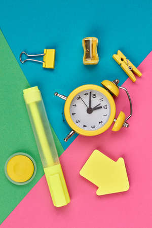 Yellow stationery supplies on color background. Alarm clock and school items on colorful paper background. Imagens