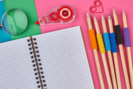 Close up school supplies on color background. Blank notebook, magnifying glass and pencils. Equipment for drawing.