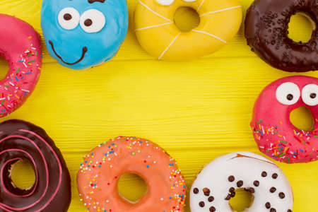 Delicious glazed doughnuts on color background. Frame with various donuts on yellow wooden table. Space for text.