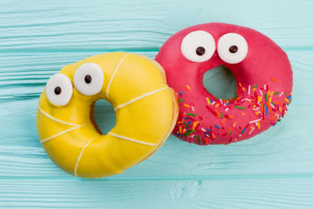 Two funny donuts on blue wooden background. Pink and yellow donuts with funny eyes.