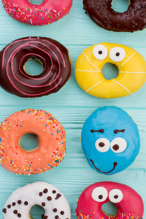 Multicolored donuts background. Various cakes with frosting on color surface. Stockfoto
