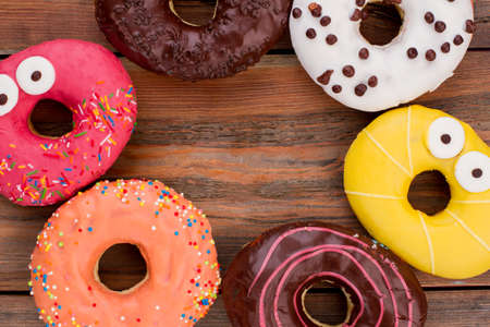 Frame with various donuts on brown wooden background. Assorted donuts on wooden table. Space for text.