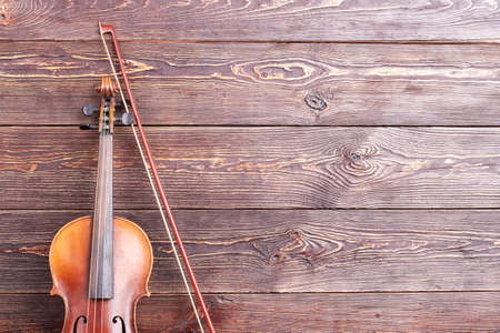 Vintage violin and text space. Musical instrument on textured wooden background and copy space.