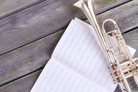 Old trumpet on musical notes sheet. Musical notes and vintage trumpet on wooden background with copy space. Stock Photo