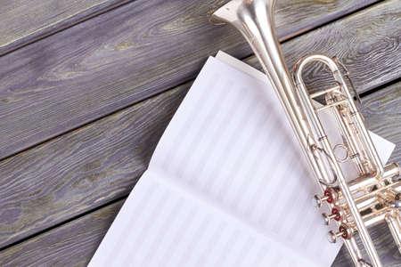 Trompeta vieja en la hoja de notas musicales. Notas musicales y trompeta vintage sobre fondo de madera con espacio de copia.