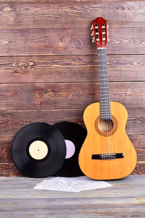 Vinyl records, guitar and musical notes. Vintage musical objects on wooden background and copy space.