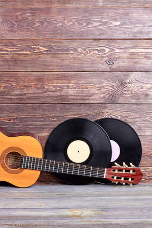 Musical instuments on vintage wooden background. Acoustic guitar and two vinyl records on wooden boards with copy space. Retro music background. Foto de archivo