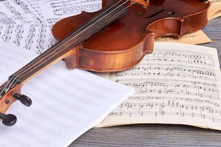 Sheets of musical symbols and violin. Viola on musical notes sheets. Musical instrument of orchestra.
