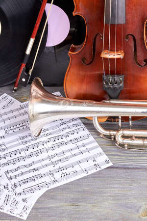 Vintage violin, trumpet and musical notes. Composition from musical instruments on wooden background. Music still life.
