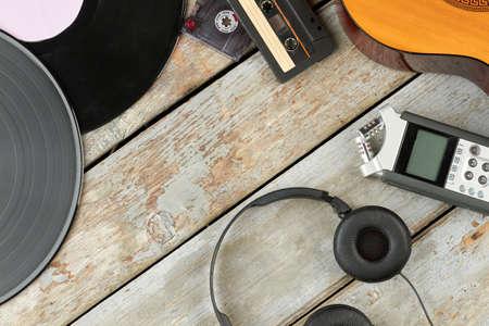Alte und moderne Audiogeräte. Holzhintergrund mit Vinyl-LP-Schallplatten, Audiokassetten, Akustikgitarre, Diktiergerät und Kopfhörern. Arbeitsraum des Musikers. Standard-Bild