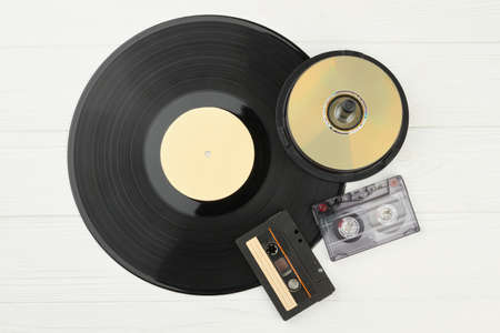 Vinyl plate, DVD discs and audio tapes. Gramophone record, compact disks and audio cassettes on white wooden background.