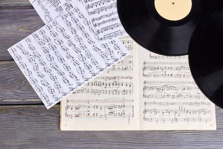 Vinyl records with music sheet scores. Musical notes sheets on wooden background. Musical background in retro style. Stockfoto