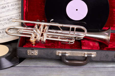 Musical background with vintage instruments. Trumpet in velvet case, vinyl records and musical notes on wooden background.
