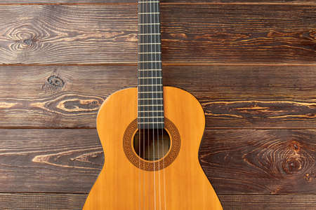Acoustic guitar on dark wooden background. Ukulele on brown wooden surface. How to play country guitar.