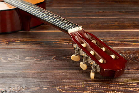 Head of guitar on textured wooden surface. Fretboard of acoustic guitar, horizontal image. Stock fotó