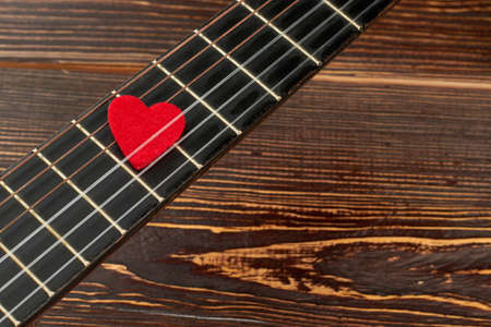 Guitar fretboard with red heart. Small red heart on acoustic guitar and copy space. Melody of love.