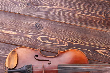 Old violin with copy space on top. Brown violin on textured wooden background, cropped image. Musical equipment in vintage style.