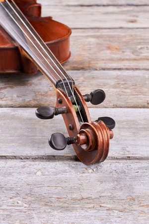 Four string violin close up. Violin scroll design. Musical instrument on wooden background, vertical image. Close up construction of violin.