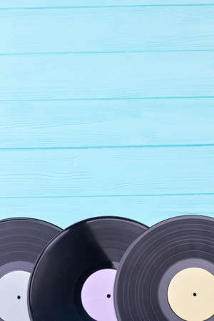 Vinyl discs with copy space on top. Set of vintage record albums on colored wooden surface. Retro media equipment.