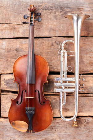 Violin and trumpet on wooden boards. Old cello and trumpet on wooden planks, vertical image. Musical instruments of symphony orchestra.