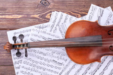Violin on musical notes sheets. Old violin and musical notes pages, cropped image. Fingerboard of violin.