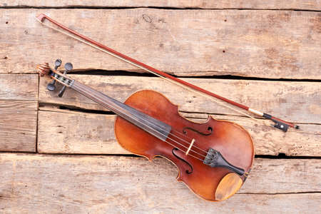 Old violin and fiddle stick. Vintage violin on rustic wooden boards. Musical instrument of orchestra.