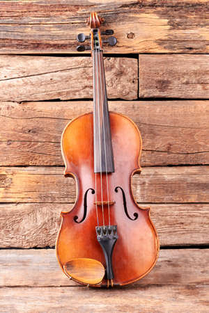Classical violin on old wooden boards. Stringed musical instrument of vintage style.