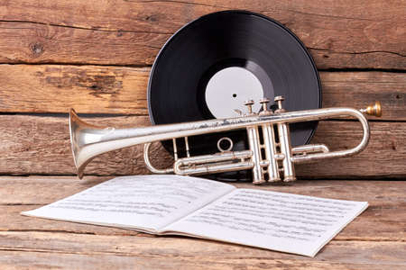 Trumpet and musical papers on old wood. Vintage musical equipment. Classics music concept. Stock fotó
