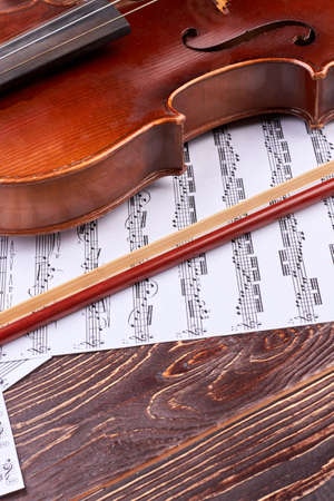 Violin, bow and musical notes sheets. Brown violin and musical notes on wooden surface, vertical image. Detail of violin waist. Orchestra instrument background.