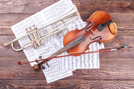 Trumpet and violin on wooden background. Musical notes, volin, bow and trumpet, top view. Classical instruments of orchestra.