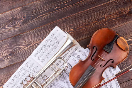Musical instruments of orchestra and copy space. Old violin, trumpet and musical notes on brown wooden background, horizontal image. Classical music study.