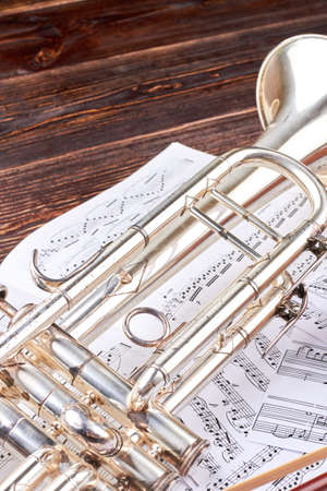 Trumpet and musical notes, vertical image. Music note sheets and trumpet on wooden background. Classical music equipment.