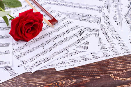 Musical sheets and rose on wooden background. Violin bow, musical papers and red rose. Love is the music.
