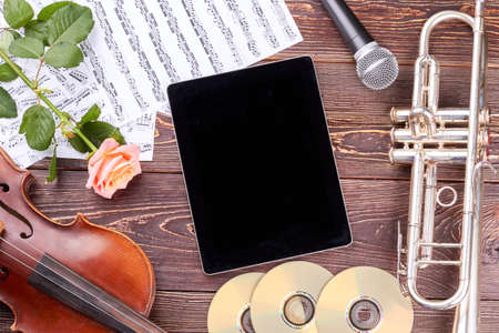 Classical music background with instruments and flowers. Pc tablet, violin, trumpet, microphone, discs, musical notes and rose on wooden background.