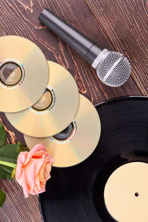 Wooden background with musical objects. Vinyl record, blank cd or dvd discs, microphone and rose. Music still life. Stock Photo
