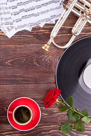 Wooden background with musical equipment. Musical notes, trumpet, vinyl record, red rose and cup on wooden background with copy space, vertical image. Stock Photo