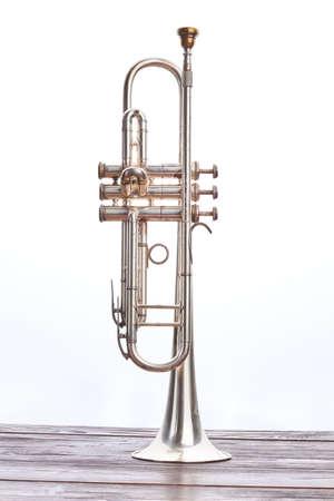 Instrumento de trompeta sobre fondo blanco. Trompeta de mesa de madera, imagen vertical. Instrumento vintage de música clásica.