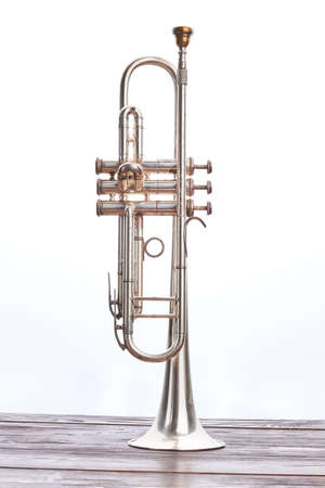 Trumpet instrument over white background. Trumpet on wooden table, vertical image. Vintage instrument of classical music.