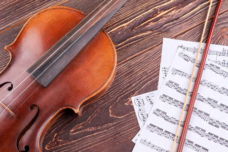 Violin and musical notes on wooden background. Brown vintage violin, bow and musical notes on brown wooden table close up. Classical music background.